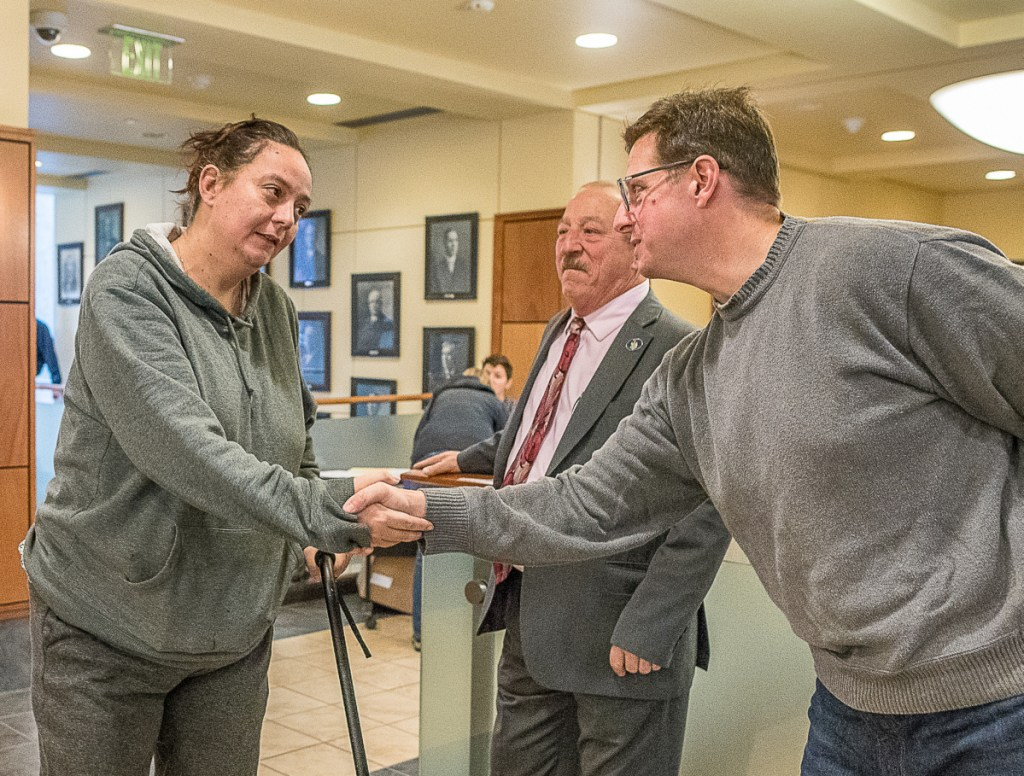 Amy Osborne is greeted by District Attorney Andrew Robinson, far right, early Tuesday morning at Auburn City Hall. Rep. Bruce Bickford, center, also was greeting voters.