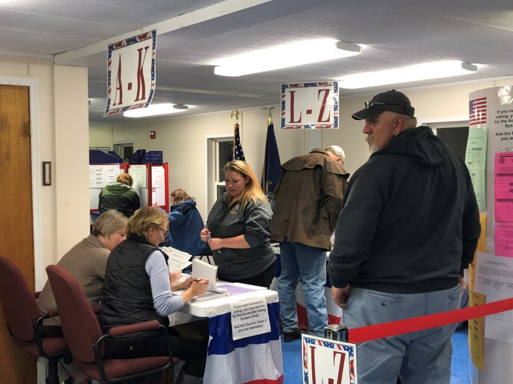 China deputy election clerks Traci Britten, left, and Julie Finley prepare a ballot Tuesday night for Myriah Cotter at the portable building near the Town Office.