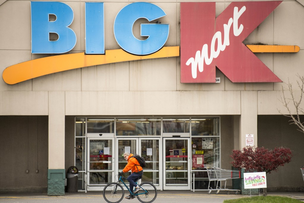 A shopper rides by the Kmart store Friday at Elm Plaza on Main Street in Waterville.
