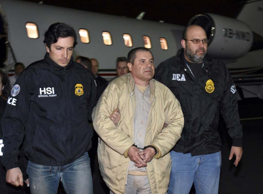 """Authorities escort Joaquin """"El Chapo"""" Guzman from a plane in January 2017 at Long Island MacArthur Airport in Ronkonkoma, N.Y., after he was extradited from Mexico. His drug conspiracy trial begins Monday in New York City."""