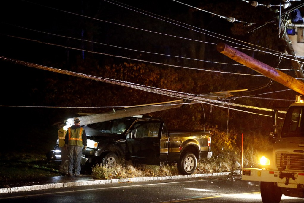 Line workers examine the base of a utility pole and the truck that hit it Tuesday on outer Congress Street. A portion of the road was closed during the repair. Power was out at the Portland International Jetport and nearby areas.