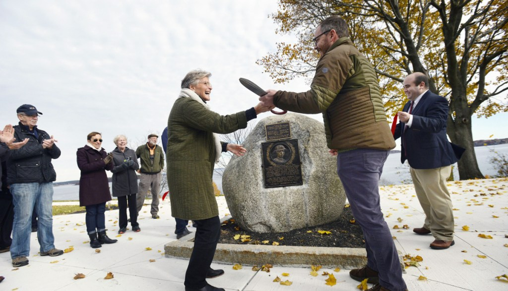 Patsy Wiggins, executive director of Friends of the Eastern Promenade, and Ethan Hipple, deputy director of Portland Parks, Recreation & Facilities, hold a giant pair of scissors after cutting the ribbon during the dedication of the Jacob Cousins Memorial on the Eastern Promenade in Portland on Friday.