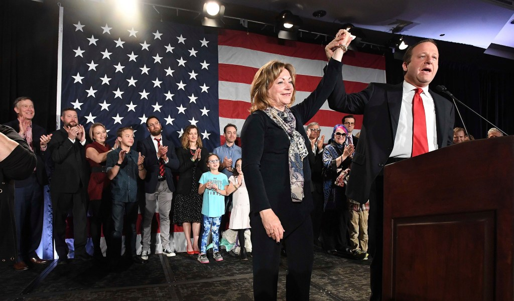 Colorado Governor-elect Jared Polis, right, lifts the hand of Lt. Governor-elect Dianne Primavera during his acceptance speech at the watch party for Colorado Democrats at the Westin Hotel in downtown Denver, Tuesday, Nov. 6.