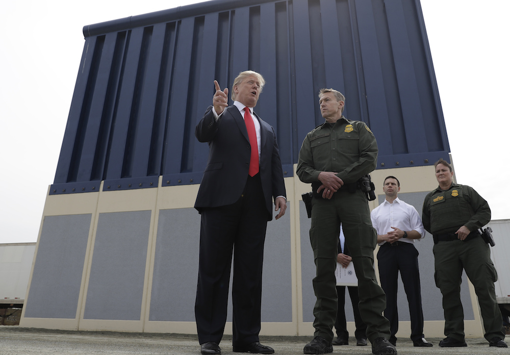 President Donald Trump in front of a border wall prototypes in San Diego in March