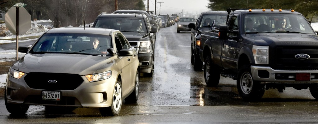 """As students and staff leave Skowhegan Area High School on Monday, state police Det. Bryant Jacques, in unmarked cruiser at left, also leaves the school grounds following a posted threat to the school. """"I did some drive-through passes at the school today to let students know we (law enforcement) are present,"""" Jacques said."""