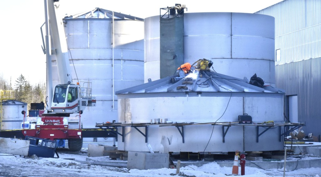 Workers weld one of the anaerobic digesting system tanks beside the Fiberight Corp. solid waste processing and recycling facility under construction in Hampden on Thursday.