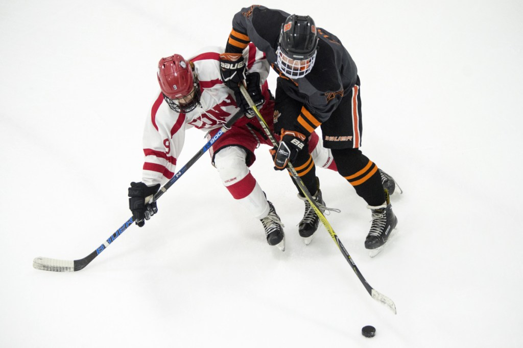Cony's Vinny Manocchio, left, battles for the puck with Brunswick's Henry Burnham last week at the Camden Nation Bank Ice Vault in Hallowell.