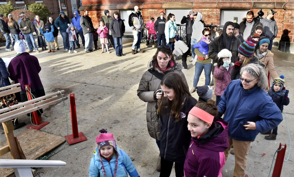 More than 60 parents and children wait in line Dec. 16 to see Santa at Kringleville in Waterville.