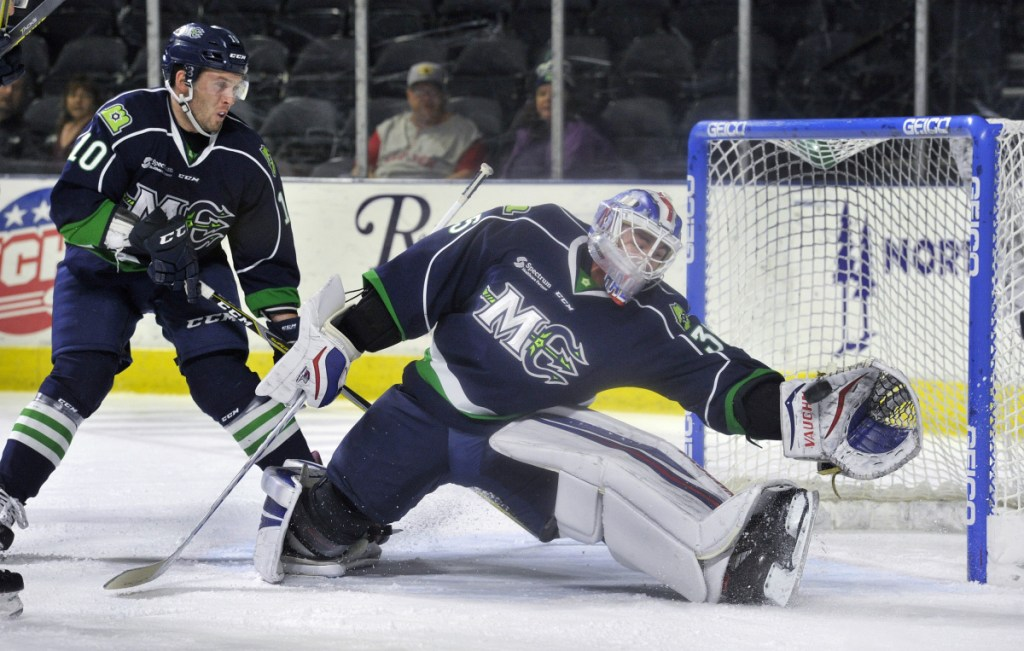 Mariners goalie Brandon Halverson makes a glove save in the first period Sunday as teammate Riley Bourbonnais looks on. Halverson made 40 saves, his second-highest total of the season, helping Maine secure a 4-2 victory at Cross Insurance Arena.