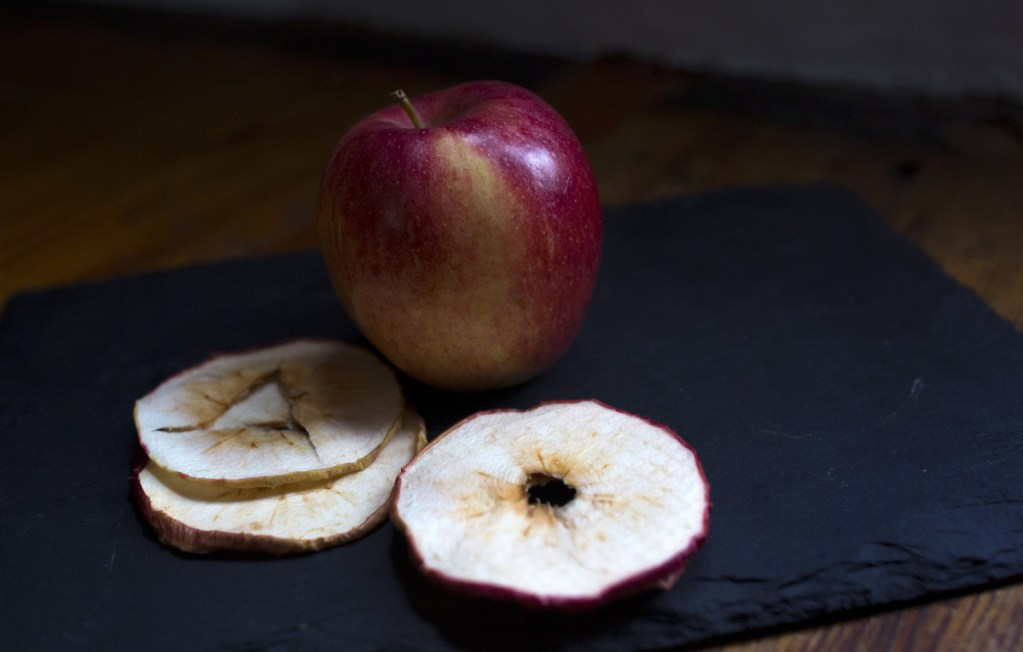 A fresh apple and dried apple slices from Applewald Farm stall in the Brunswick Winter Market. The flavor of dried fruit is concentrated, so only a small amount is required to get the desired result in a recipe.