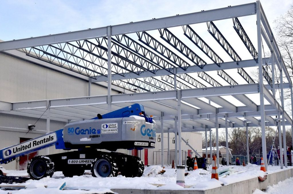 As children play on an outdoor playground, background, workers erect steel girders Thursday for the new Family Wellness Center at the Alfond Youth Center on North Street in Waterville. The building permit for the structure was discounted, which private developer Paul Lussier criticized at Wednesday's City Council meeting.