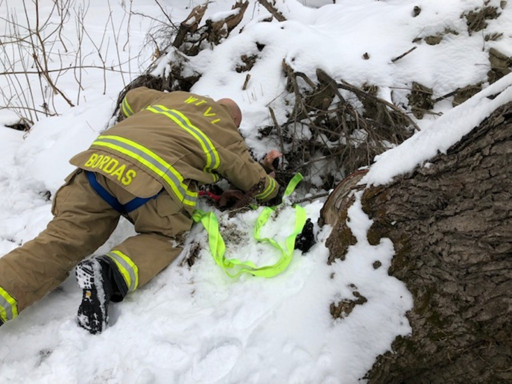 Waterville fire-rescue technician Glen Bordas lies on the ground Jan. 5 as he talks calmly to the boy, who slipped into a hole, and explains to him how they plan to get him out by strapping webbing around his body and pulling him slowly upward.