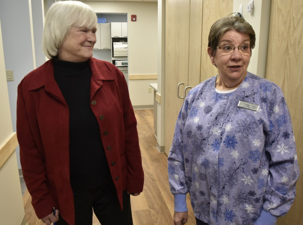 Dr. Barbara Covey, left, chairman of the board of the Waterville Community Dental Center, listens on Wednesday as dental hygienist Hope Ricker points out the benefits of the new facility located in FirstPark in Oakland, including the larger space and more accessible parking.