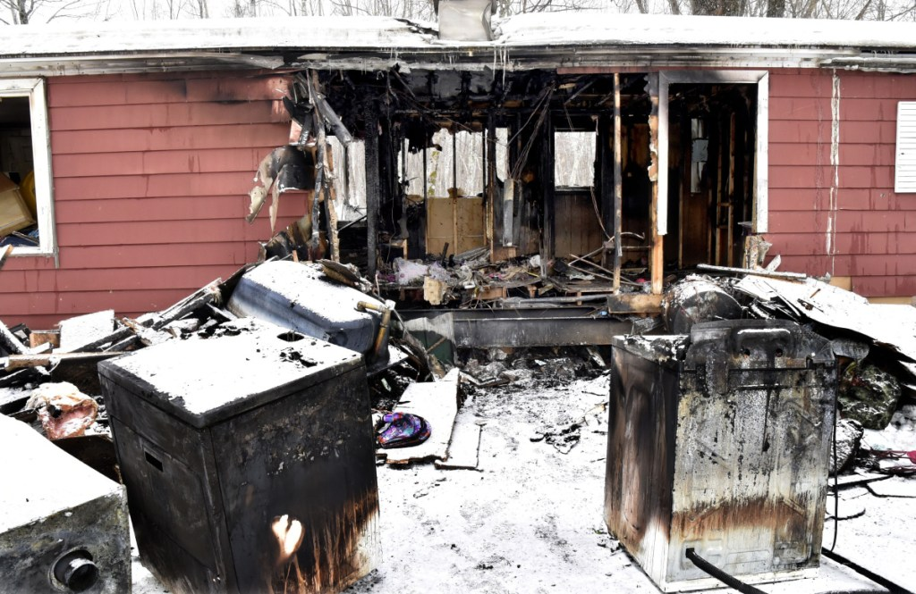 """Burned appliances pulled through a gaping hole in this mobile home Tuesday populate the yard Wednesday at the site of a home fire in Cornville. Louis Wheeler Jr., the owner of the 733 East Ridge Road home in Cornville, said he wanted to credit firefighters for their efforts in a dangerous situation. """"Those firefighters are animals,"""" Wheeler said."""