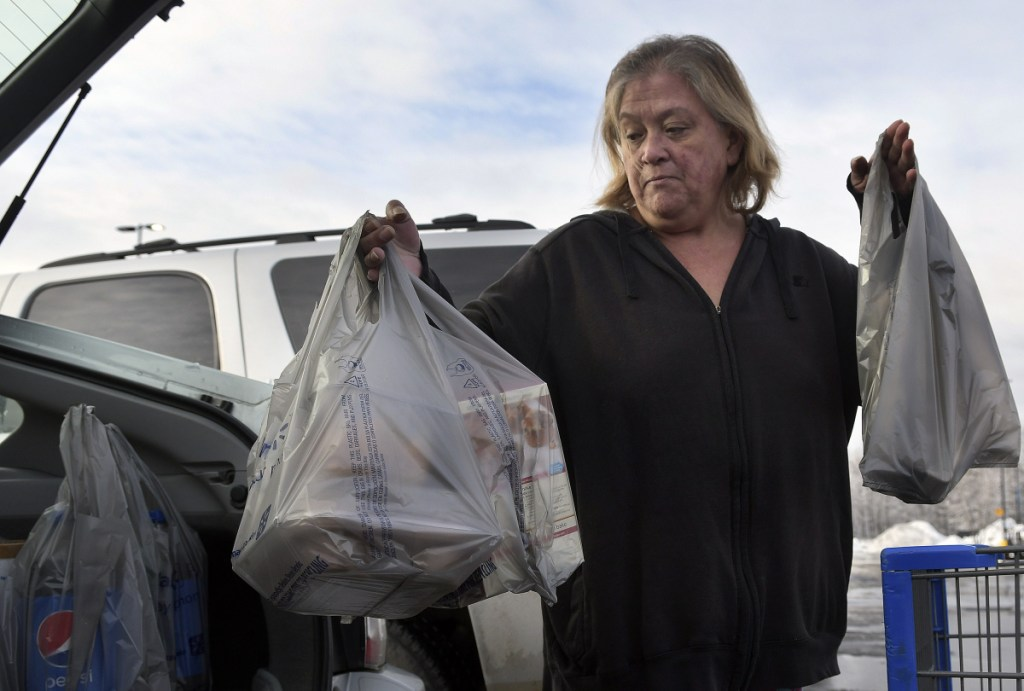 Earlinda Nirza, of Augusta, gathers plastic bags full of groceries Jan. 10 after shopping at Walmart in Augusta. City councilors in Augusta discussed on Thursday night a proposal to impose a 5-cent fee on each bag used by customers of large retailers, but councilors' reactions to the measure suggest it is unlikely to pass.