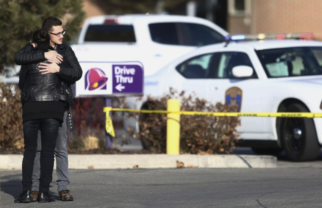 A man and woman embrace as police investigate a shooting at the Fashion Place mall in Murray, Utah on Sunday.
