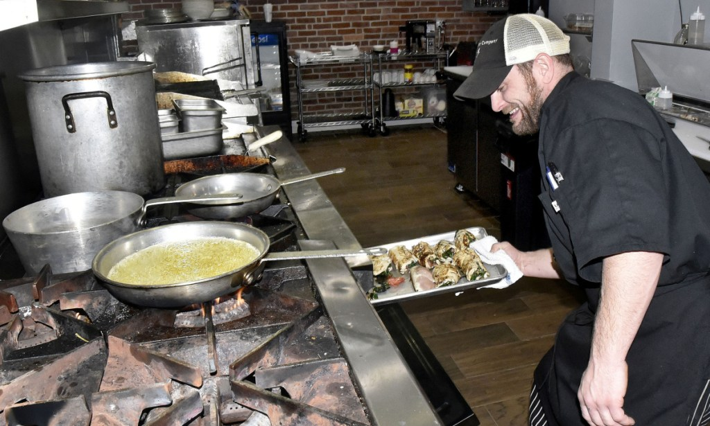 Opa restaurant head chef Joe Kenny places stuffed chicken in an oven Tuesday at the Greek restaurant on Main Street in Waterville.
