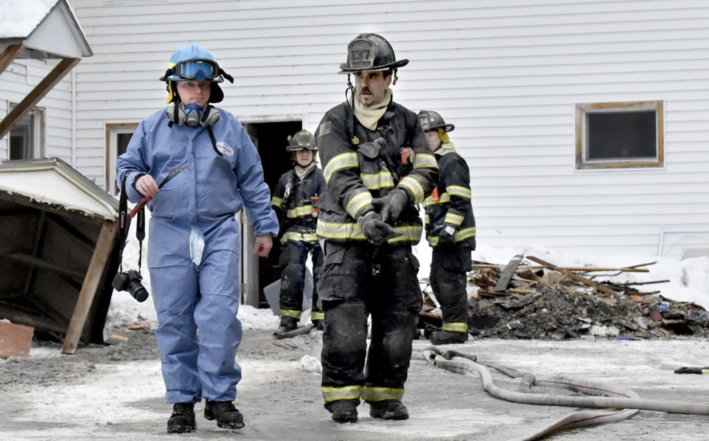 Jeremy Damren, left, of the Office of State Fire Marshal, confers with a Skowhegan firefighter Sunday while investigating the cause of a fire at 386 Water St. in Skowhegan after fire broke out there that morning.