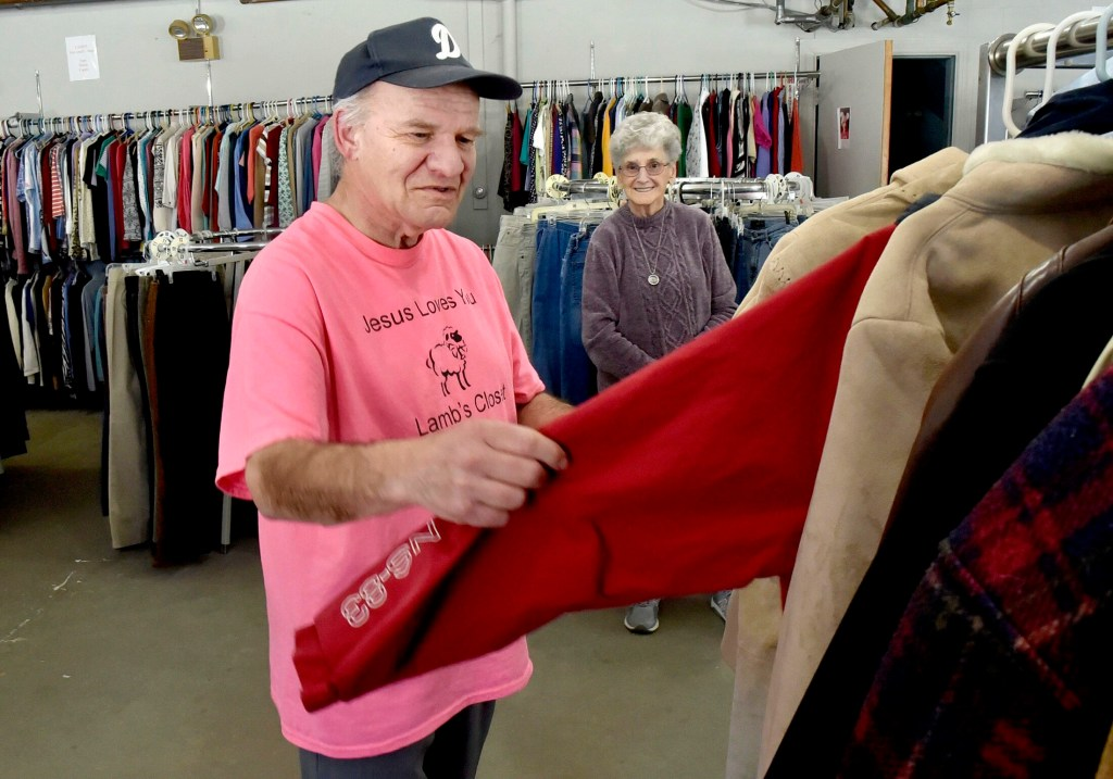 Volunteer David Scribner straightens clothing as Director Erma Blakney watches at the Lamb's Clothes Closet at the First Baptist Church in Fairfield on Tuesday.
