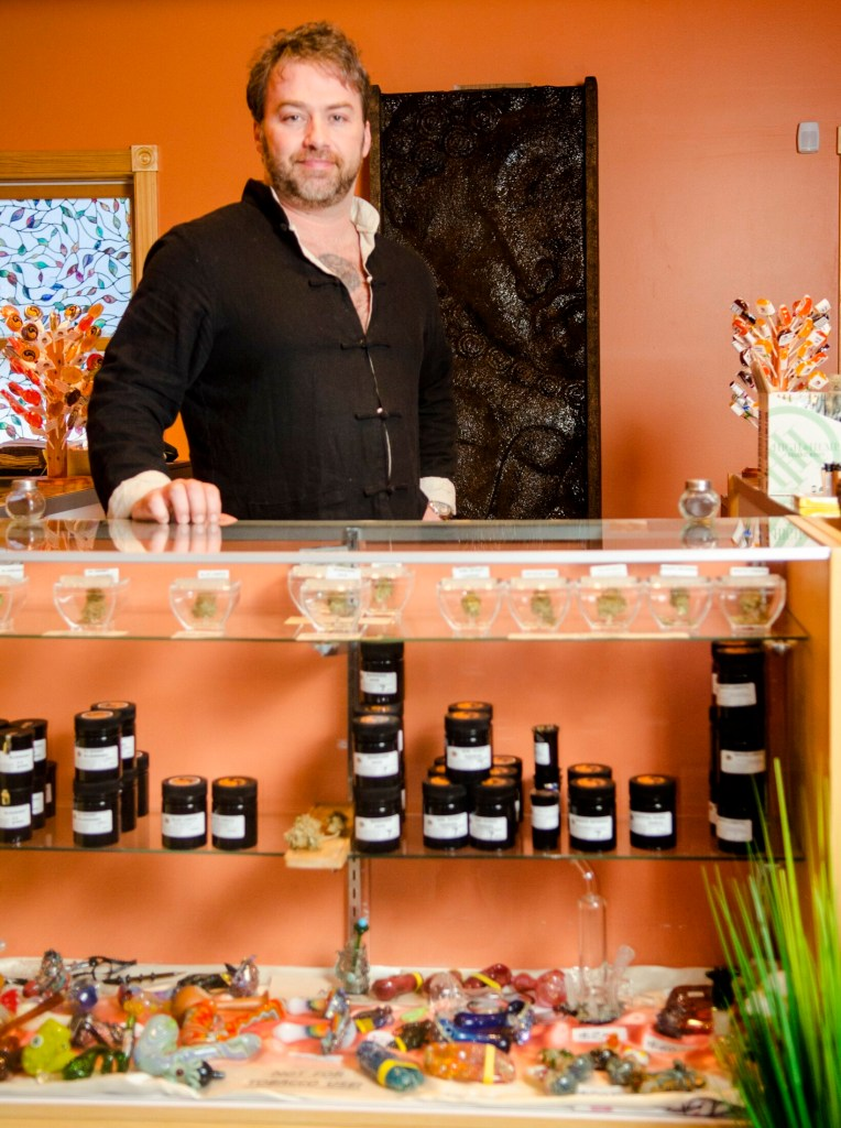 Owner Jake McClure stand behind the counter Friday at the Sensi Sensei shop in Jefferson.
