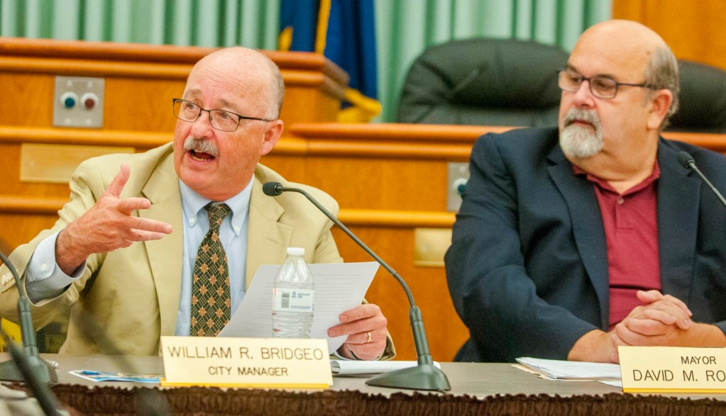 City Manager William Bridgeo speaks, while Mayor David Rollins looks on, at a city council meeting in July 2017 at City Center in Augusta.