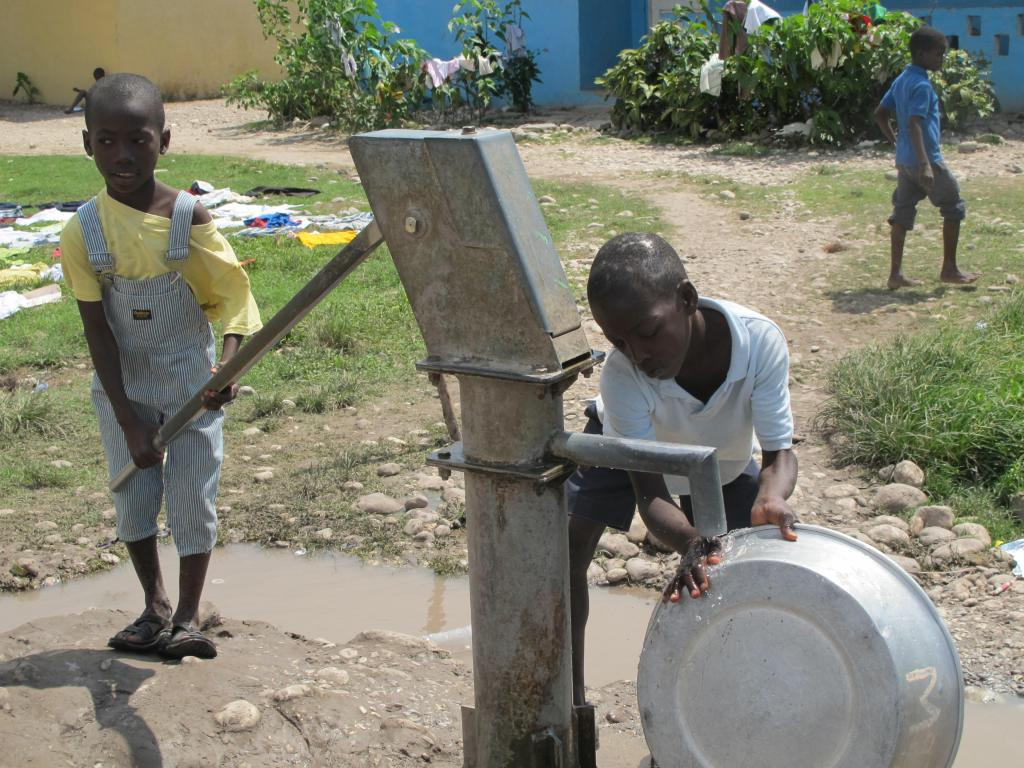 Orphan boys pump water, left, to clean a washing tub at Hope Village in Les Cayes. Almost half of the relief supplies aboard the Maine ship Sea Hunter are being delivered this weekend to the orphanage and community. assistance program.