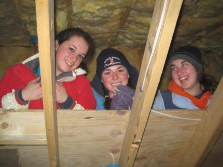 Students Katie Savidge, Kate Dodge and Mary Foster install insulation in a Habitat for Humanity home in Freeport.