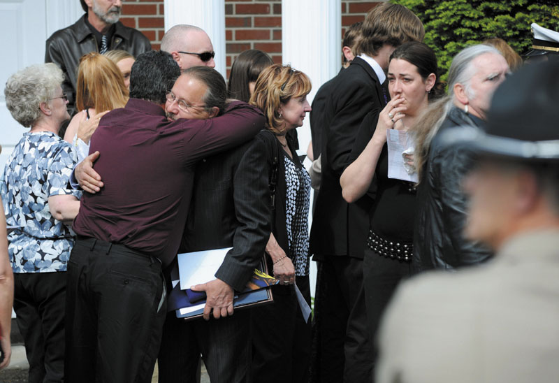 Army Spc. Wade Slack's father, Dr. Alan Slack, holds federal and state honors awarded to his son as he is greeted by family and friends following the funeral Sunday at Blessed Hope Advent Christian Church in Waterville. Wade Slack, 21, specialized in disarming explosives and died of wounds suffered May 6 in indirect fire in Jaghatu, Afghanistan.