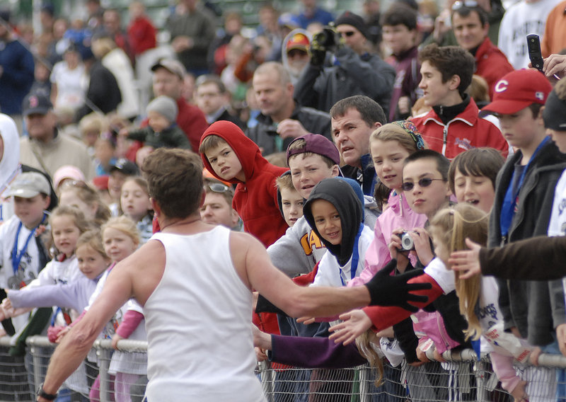A runner gets high-fives from spectators as he approaches the finish line inside Hadlock Field.