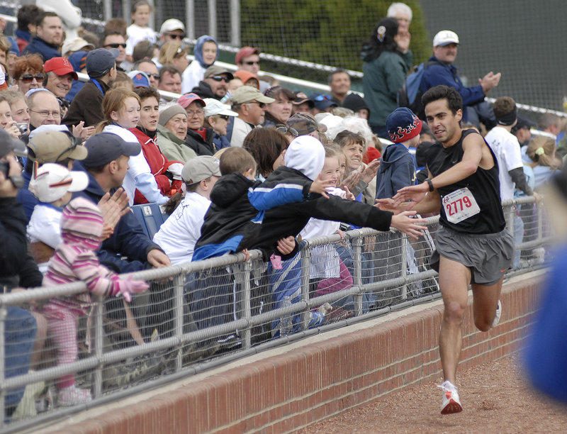 Louie Luchini of Ellsworth is greeted by youngsters as he approaches the finish line Sunday as the winner of the Sea Dogs Mother's Day 5K.