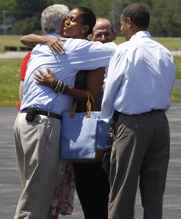 First lady Michelle Obama hugs Rep. Mike Michaud, D-Maine, as he and President Barack Obama are greeted by Maine Gov. John Baldacci.