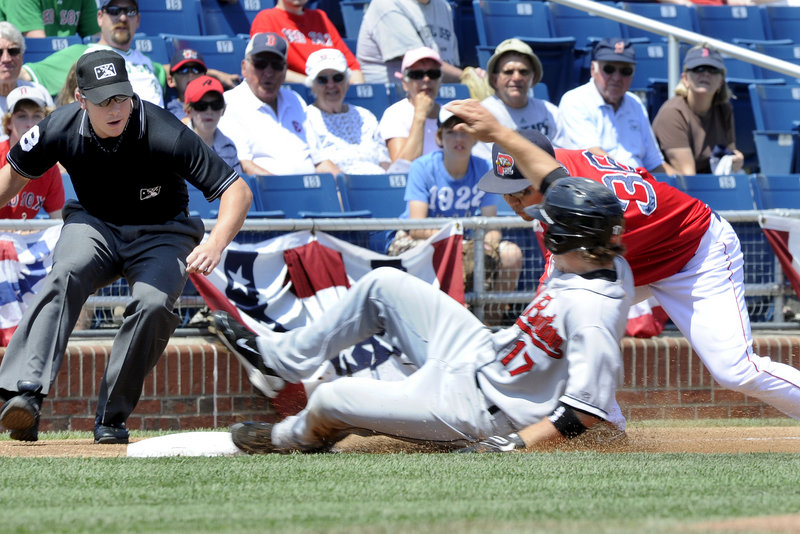 New Britain's Joe Benson is tagged out at third by Portland's Ray Chang after trying to steal in the first inning Monday at Hadlock Field. The Sea Dogs were beaten 4-3 and enter the All-Star break 10 games out of first place.