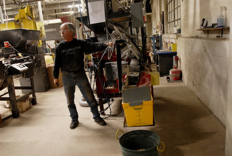 "Longtime employee Foster Davis demonstrates an automatic sorter at the Saunders Brothers mill in Locke Mills on Monday. ""I can get every machine running here in 10 minutes,"" he said."