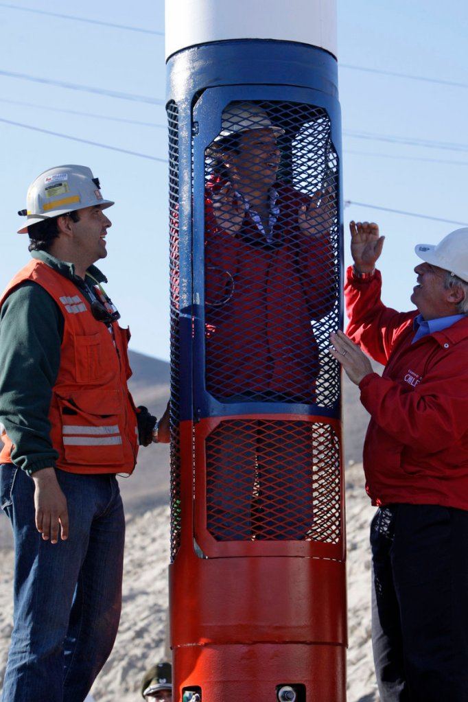 Mining Minister Laurence Golborne stands inside a capsule that will be used to rescue trapped miners from the collapsed San Jose mine as rescue operation deputy Rene Aguilar, left, and Health Minister Jaime Manalich watch in Copiapo, Chile.