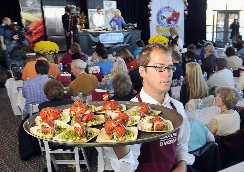 Justin Dewalt carries a tray laden with servings of the winning lobster dish created by Kelly Patrick Farrin, seen on the stage, in the Lobster Chef of the Year competition at Portland's Ocean Gateway on Friday. Farrin is chef at the Azure Cafe in Freeport.