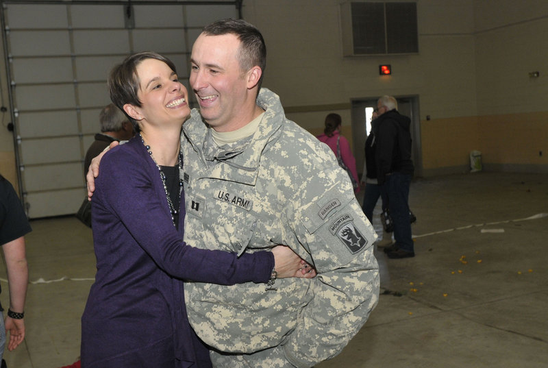 Capt. Paul Bosse of Auburn is reunited with his wife, Loriann, in Bangor on Thursday when he and the Maine Army National Guard company he commands returned from Afghanistan.
