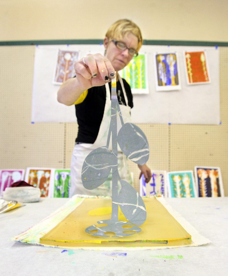 Artist Laura Dunn of Biddeford removes a stencil pattern as she creates a gelatin monotype print in the former Renys building during Saturday's Handmade Holiday Craft Fair in Biddeford.