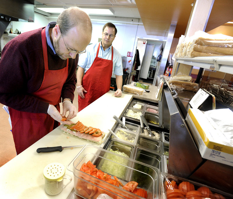 Steve Shea, right, director of operations for Amato's in Freeport, guides Ray Routhier.