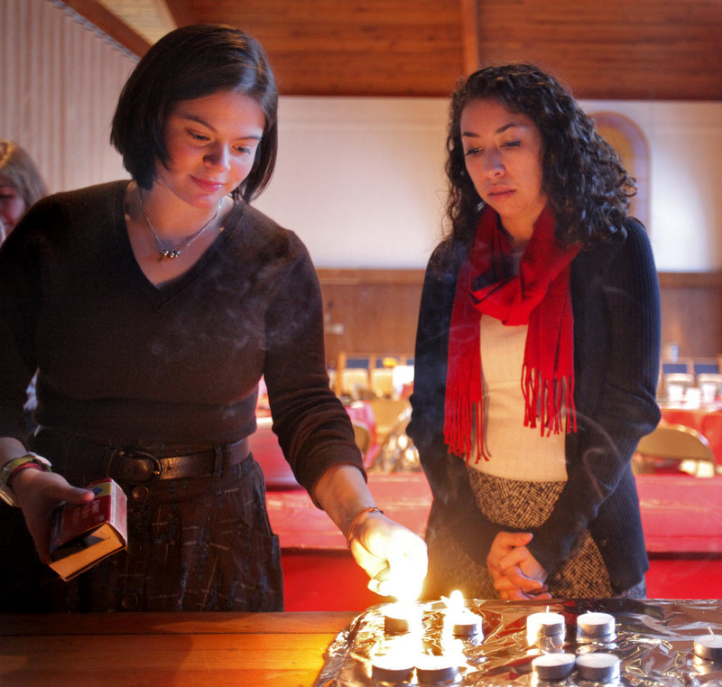Bowdoin students Lydia Singerman, left, and Shoshana Cohn, light candles before the service.