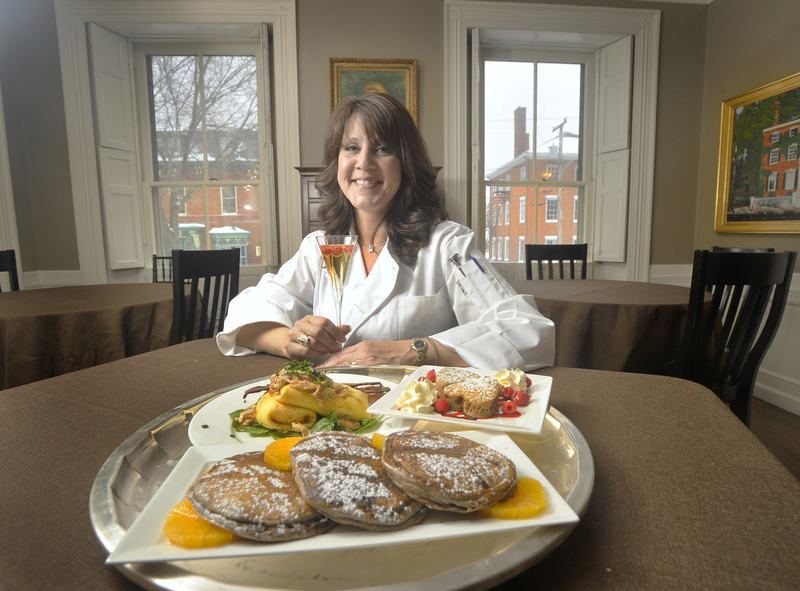 Dana Moos shows off her chocolate ricotta pancakes, including a version for the kids to help prepare for their parents, and a dish of ricotta, parmesan and asparagus crepes with Maine crab and sherry butter served with candied pepper bacon. Moos is in the dining room of the Danforth Inn on Portland's West End.