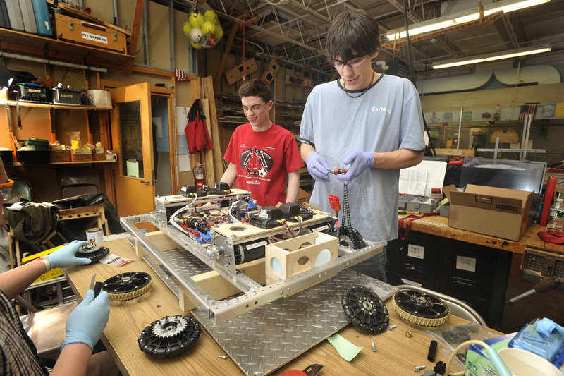 South Portland s robotics team captain Jacub Emery, right, and several teammates, including Gilead Biggie, work on attaching the wheels and chain drive onto a robot.