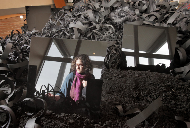 "Artist Lauren Fensterstock is reflected in a Plexiglas panel that is part of her ""Incidents of Garden Displacement"" last week as she installs the sculptural garden made of black paper, charcoal and reflective squares at the Ogunquit Museum of American Art. The seaside museum in Ogunquit reopens for the season on May 1."