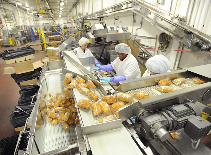 Workers at AdvancePierre's Portland plant  package stuffed chicken breasts along a production line in May 2014. The frozen entree division has become one of the most profitable for the company.