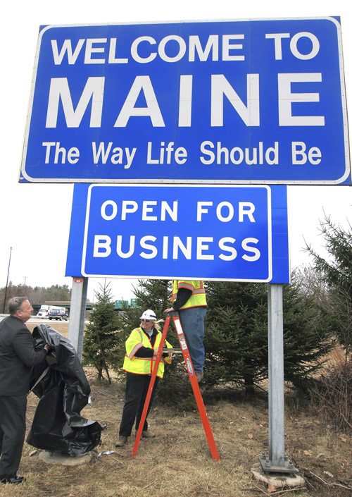 "In this March 18, 2011, photo, Gov. Paul LePage, left, unveils the ""Open for Business"" sign along Interstate 95 in Kittery."