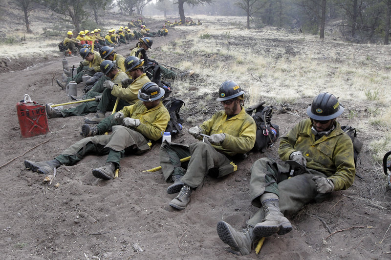 Firefighters sharpen their tools as they prepare for a back burn operation in Eagar, Ariz., on Wednesday. Winds could drive a wildfire into New Mexico, where residents of the town of Luna prepared to evacuate Thursday. Authorities said there was no containment in sight.
