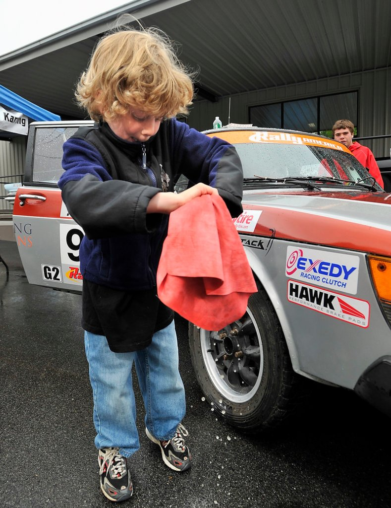 """Rhys White, 8, left, wrings out a towel after wiping his father's Saab 900 at the """"Calling All Cars"""" show Saturday at the Portland Motor Club."""