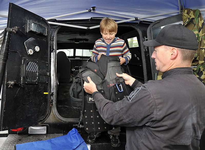"""Adrian Boothby, 6, of Portland checks out a bullet-proof vest held by Portland police Sgt. Chuck Libby. Adrian is standing in the armored """"Peacekeeper,"""" which holds 12-14 officers and is built on a Ford F350 truck chassis."""