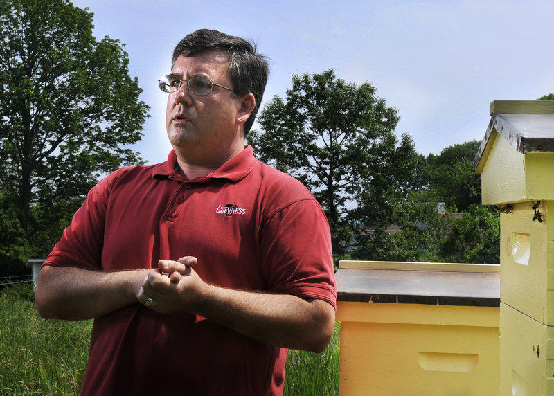 Phil Gaven, standing near two of the four hives he keeps on a friend's property in South Portland on Tuesday, is fighting to change city ordinances that restrict the scope of beekeeping.