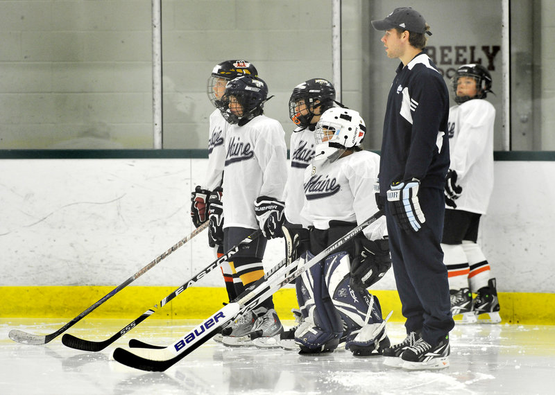 Will O' Neill, a captain on the University of Maine hockey team, listens to instructions before conducting a drill with youngsters at the Black Bear Hockey Camp at Falmouth Ice Center.