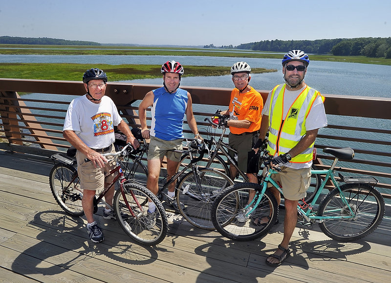 From left, Tom Daley, founder and trustee for Scarborough Eastern Trail Alliance; Stewart; John Andrews, retired president and founder of the Eastern Trail Alliance; and Hamblen pause to celebrate after crossing the bridge over the Scarborough Marsh.